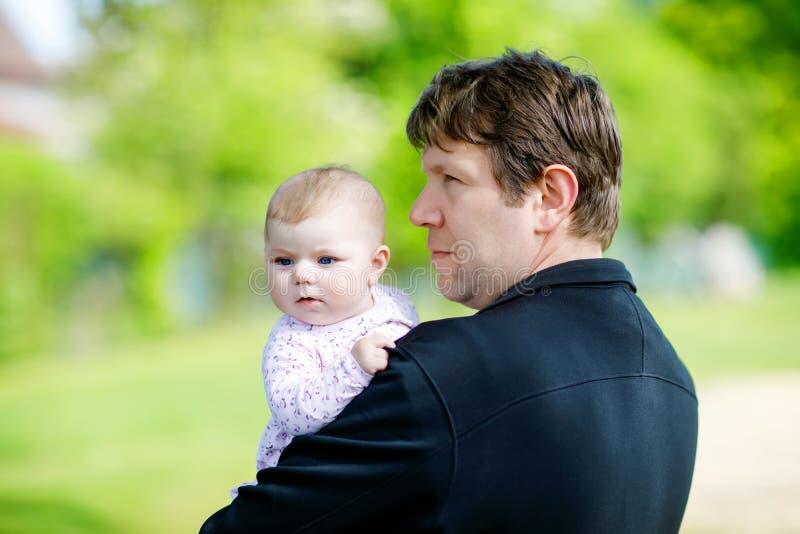 Jeune père fier heureux ayant l'amusement avec la fille nouveau-née de bébé, portrait de famille ensemble Papa avec le bébé dehor photographie stock libre de droits