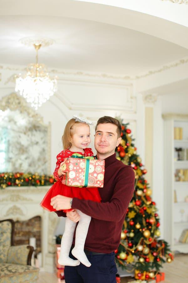 Jeune père gardant la petite fille avec le présent, arbre de Noël à l'arrière-plan image stock