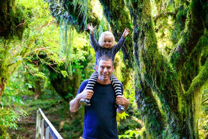 Jeune père heureux avec sa fille dans la forêt tropicale, parc national d'Egmont, Nouvelle-Zélande images libres de droits