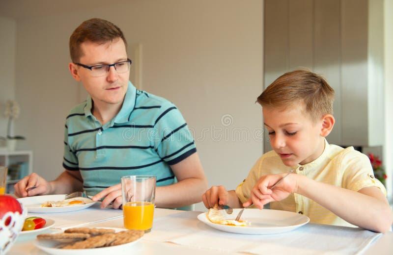 Jeune père heureux avec son petit fils parlant au petit déjeuner photo stock