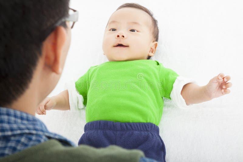 Jeune père heureux jouant avec le bébé se situant dans le lit photos libres de droits