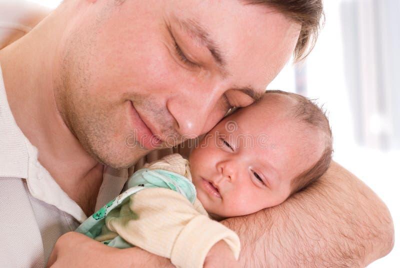 Jeune père jugeant tendrement nouveau-né image libre de droits