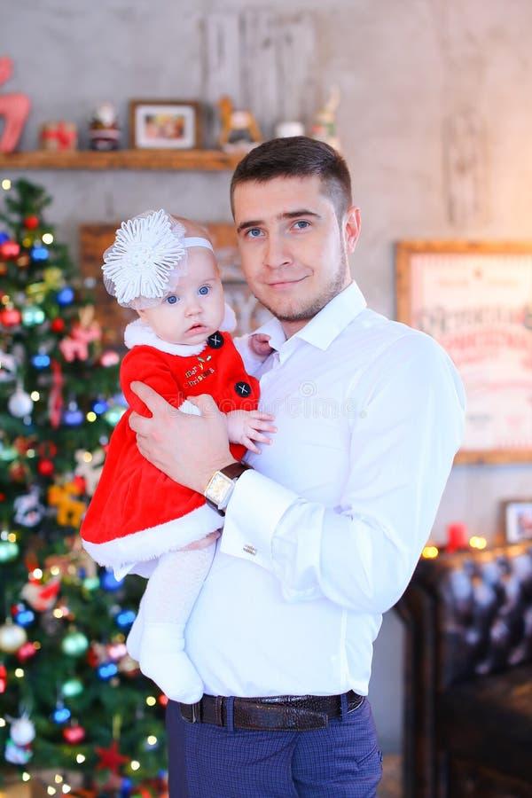 Jeune père maintenant la petite fille près de l'arbre de Noël dans le fond images stock
