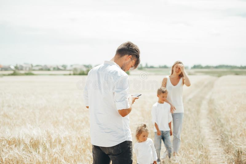 Jeune père observant quelque chose au téléphone intelligent flânant ainsi que la famille sur un champ de blé images libres de droits