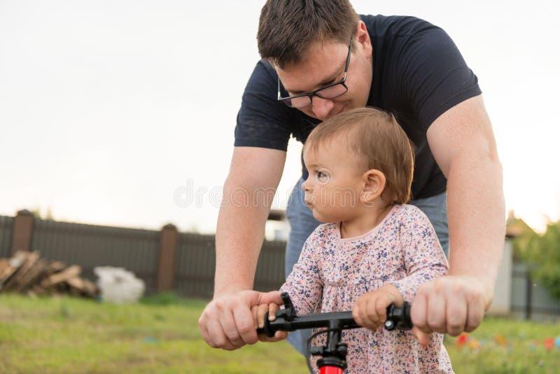 Jeune père passer le temps avec le petits un enfant de fille d'enfant en bas âge d'années et vélo mignons d'équilibre, le jour de photographie stock