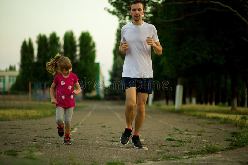 Jeune père sportif et petite fille courant dans le stade au coucher du soleil images stock
