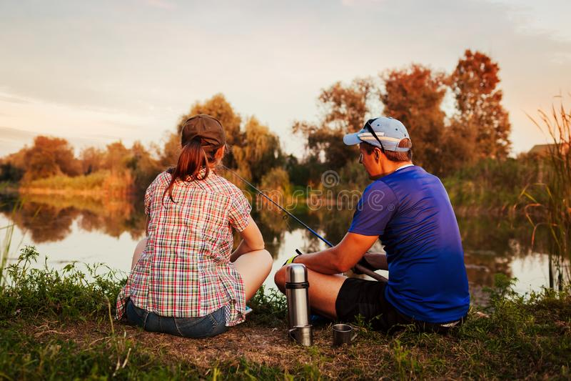 Jeune pêche de couples et thé potable sur la rivière au coucher du soleil Les gens détendant et refroidissant dehors photo stock