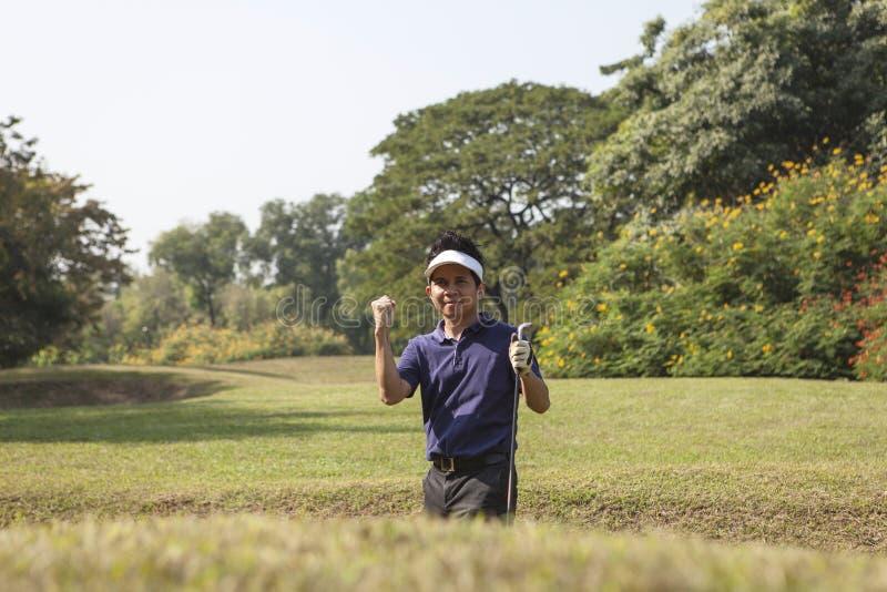 Jeune pantalon gris masculin de joueur de golf ébréchant la boule de golf hors de SA photographie stock libre de droits