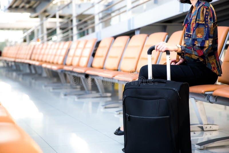 Jeune passager féminin d'aéroport avec son bagage se reposant dans le termi photos stock