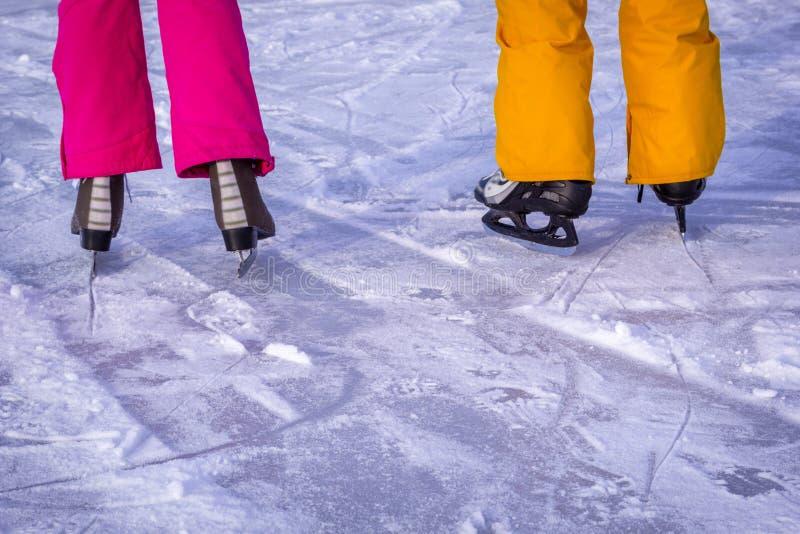 Jeune patinage de glace de couples dehors avec la neige sur le fond image stock