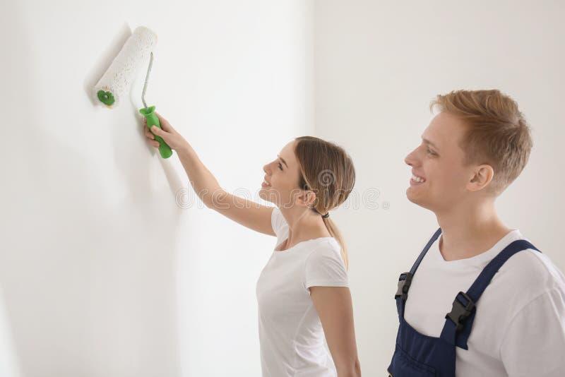Jeune peintre travaillant sous la surveillance d'agent de maîtrise dans la chambre photographie stock