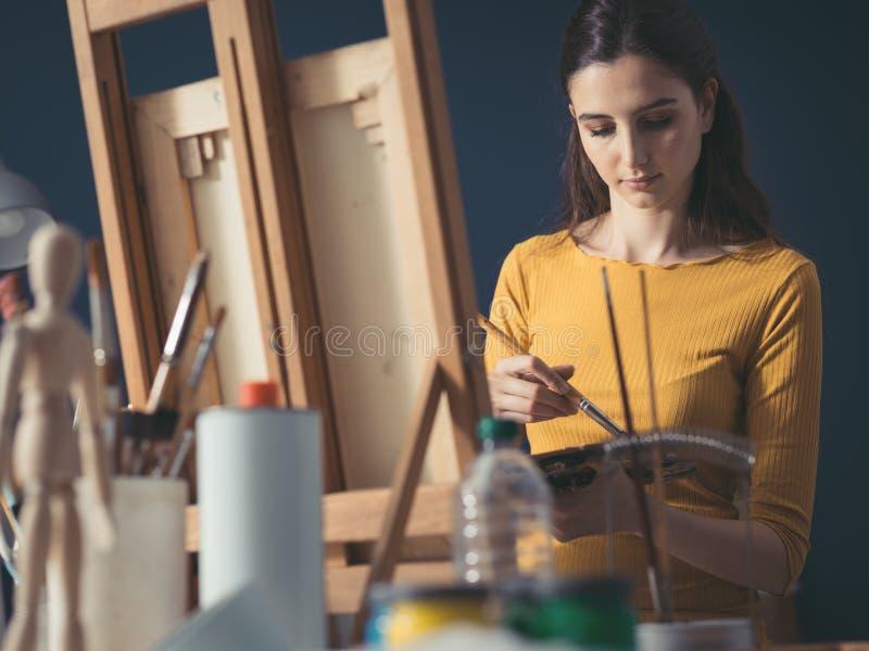Jeune peinture créative d'artiste dans le studio photos stock