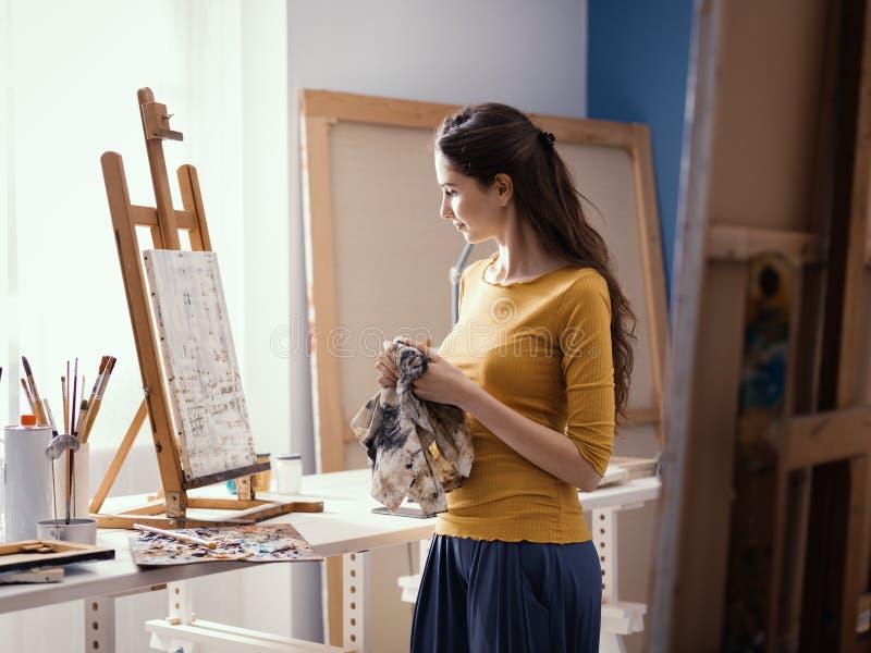 Jeune peinture créative d'artiste dans le studio images stock