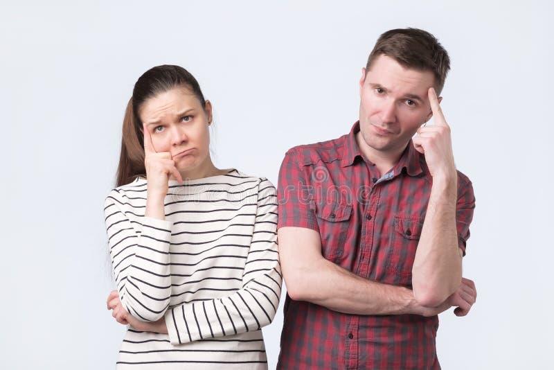 Jeune pensée attrayante de position de couples côte à côte perplexe images libres de droits