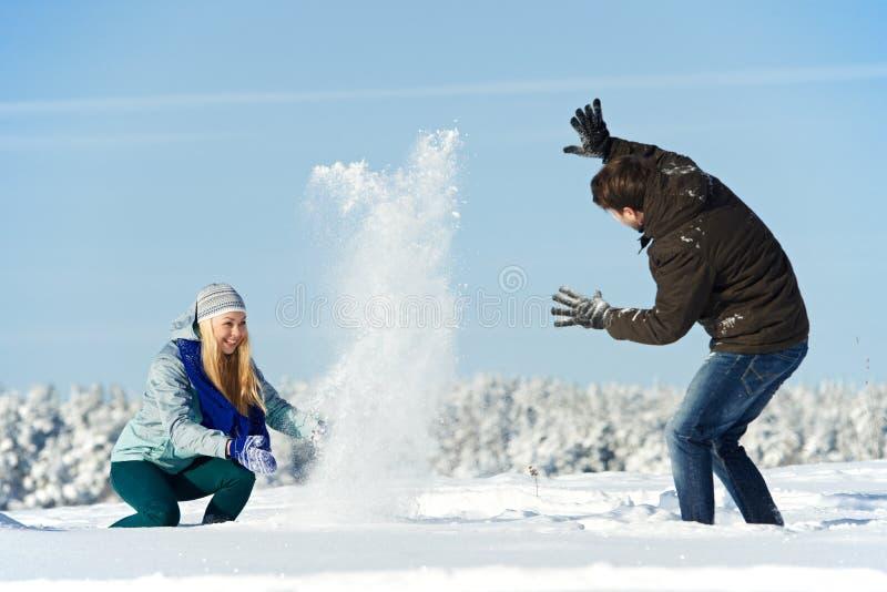 Jeune peolple jouant avec la neige en hiver photos libres de droits