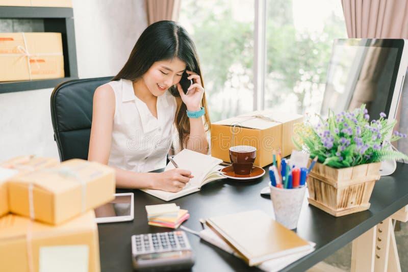 Jeune petit entrepreneur asiatique travaillant à la maison le bureau, utilisant le téléphone portable et prenant la note sur des  image stock