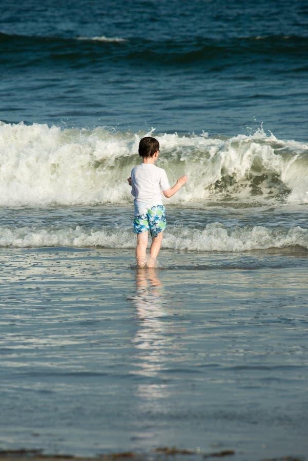 Jeune petit garçon mignon jouant au bord de la mer fonctionnant dans le ressac sur une plage sablonneuse en soleil d'été photos stock