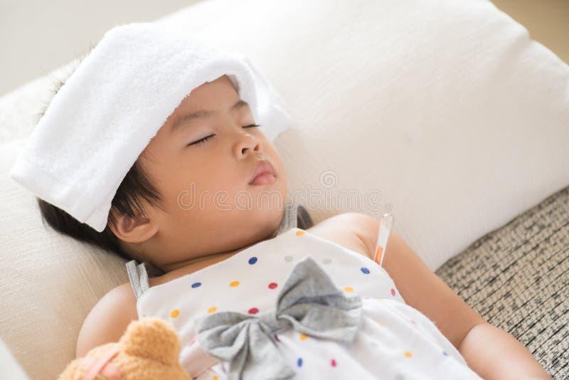 Jeune petit sommeil et malade de fille sur le sofa avec un gel plus frais image libre de droits