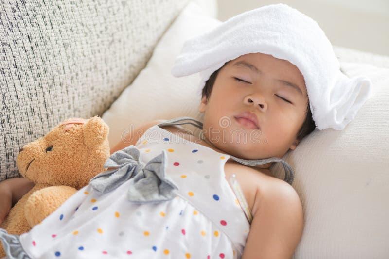 Jeune petit sommeil et malade de fille sur le sofa avec un gel plus frais photos libres de droits