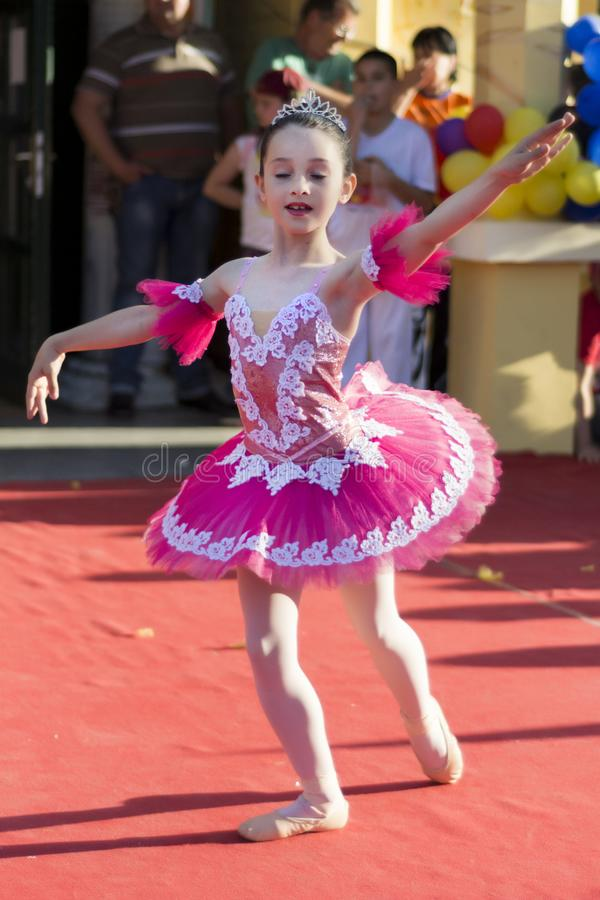 Jeune petite ballerine d'enfant dans la danse rose de robe sur l'étape publique image stock