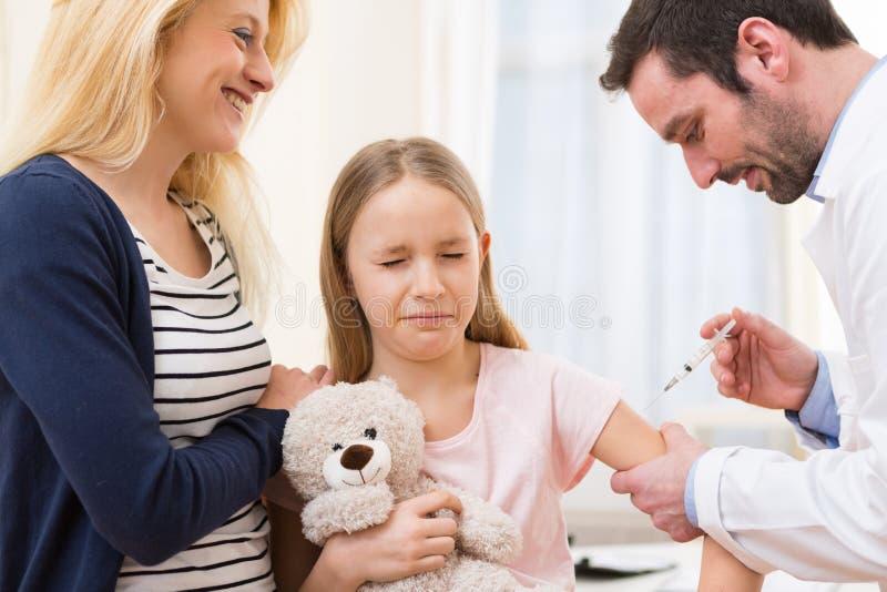 Jeune petite fille accompagnée de sa mère étant vaccinée image stock