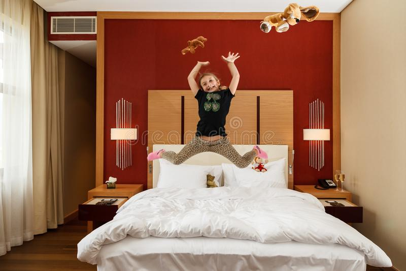 Jeune petite fille caucasienne heureuse dupant sauter dans le ciel avec ses jouets au-dessus du lit dans la chambre à coucher photo libre de droits
