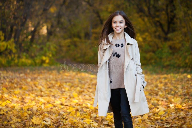 Jeune petite fille heureuse dans le manteau beige photo libre de droits