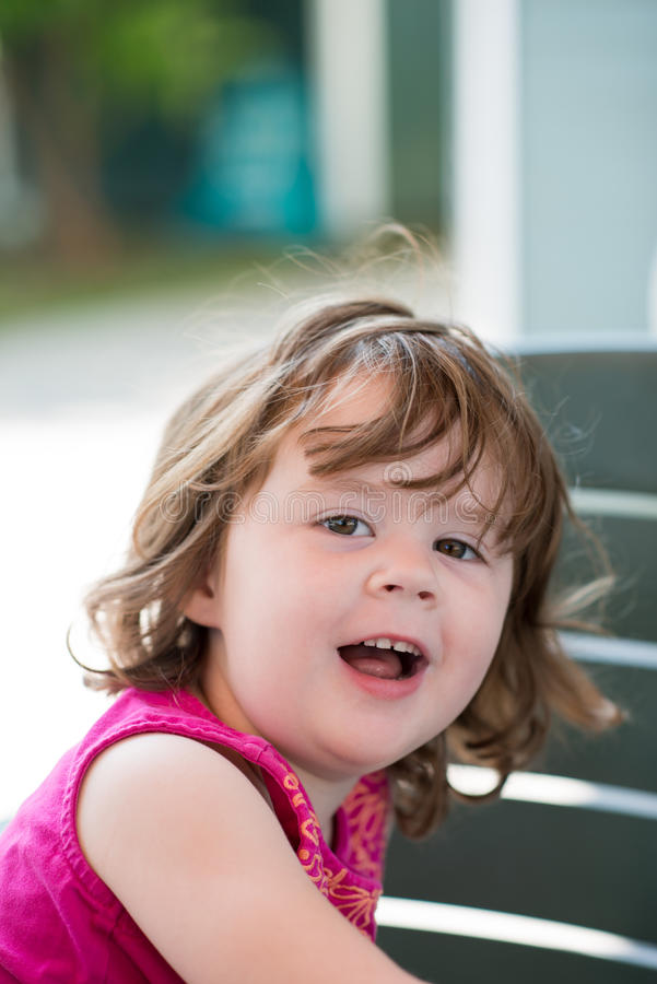 Jeune petite fille s'asseyant et semblant heureuse photo libre de droits