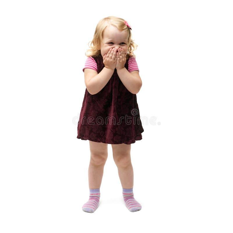 Jeune petite fille se tenant au-dessus du fond blanc d'isolement photo stock