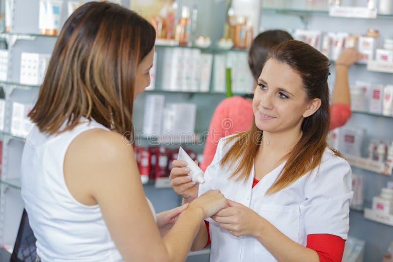 Jeune pharmacien féminin mettant la crème sur des mains de clients image libre de droits