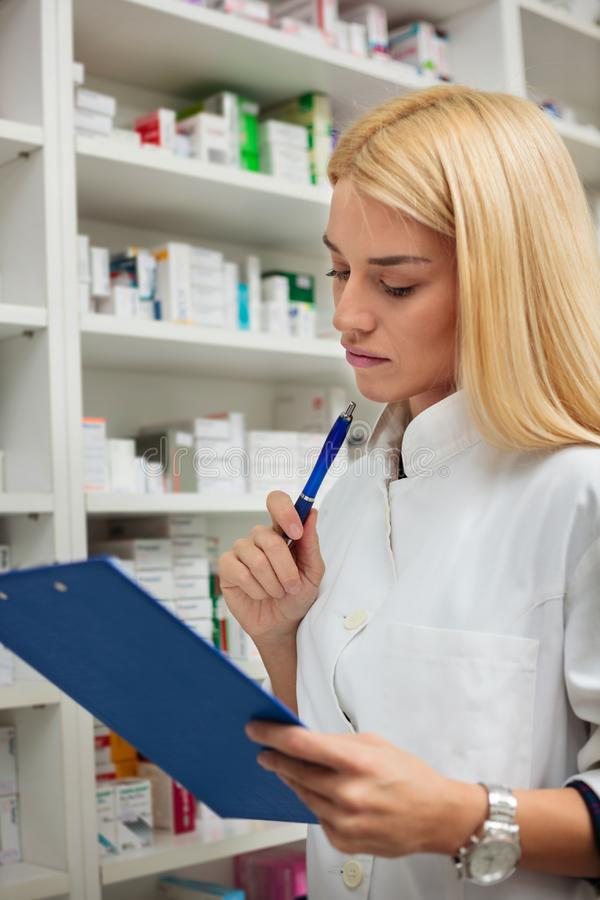 Jeune pharmacien féminin sérieux tenant un presse-papiers image stock