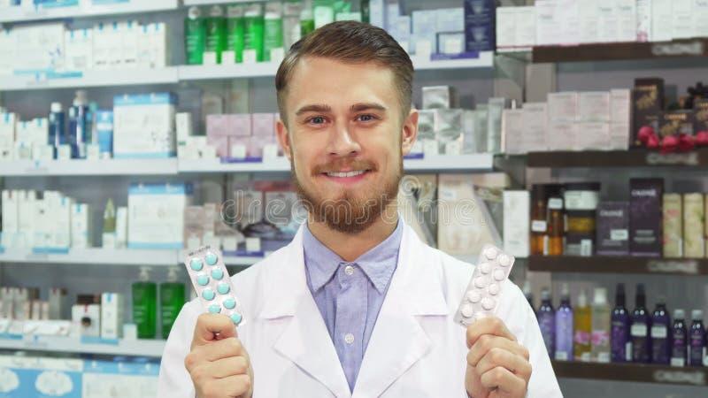 Jeune pharmacien montrant le médicament et le sourire images libres de droits