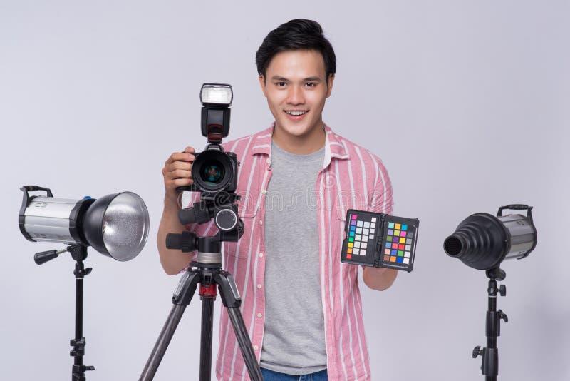 Jeune photographe asiatique tenant l'appareil photo numérique, tout en travaillant I photographie stock