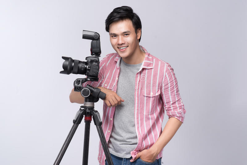 Jeune photographe asiatique tenant l'appareil photo numérique, tout en travaillant I photo stock
