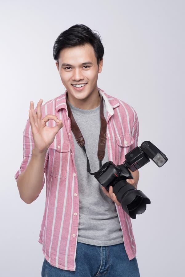 Jeune photographe asiatique tenant l'appareil photo numérique, tout en travaillant I images stock