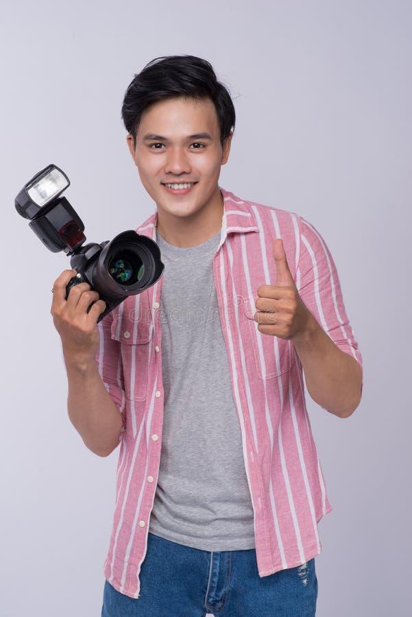 Jeune photographe asiatique tenant l'appareil photo numérique, tout en travaillant I image stock