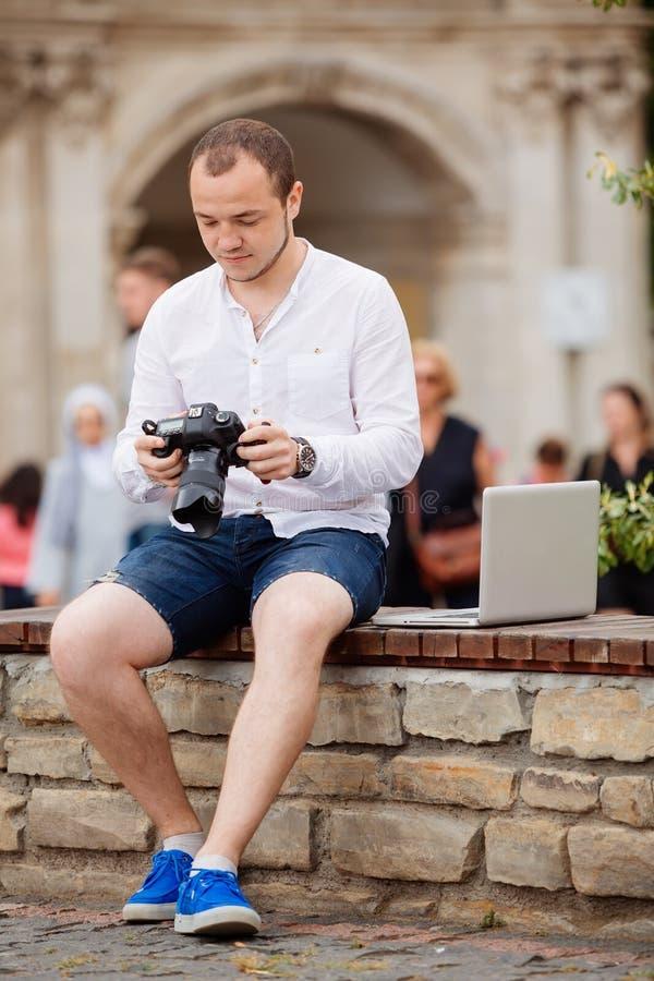 Download Jeune Photographe Avec La Photo Andtaking De Banc De Pierre De Laptopon Sur L'appareil-photo Image stock - Image du homme, regard: 76090569