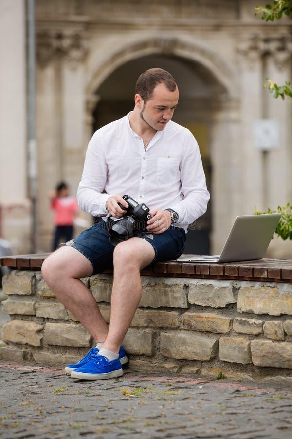 Download Jeune Photographe Avec La Photo Andtaking De Banc De Pierre De Laptopon Sur L'appareil-photo Image stock - Image du beau, laptop: 76090733