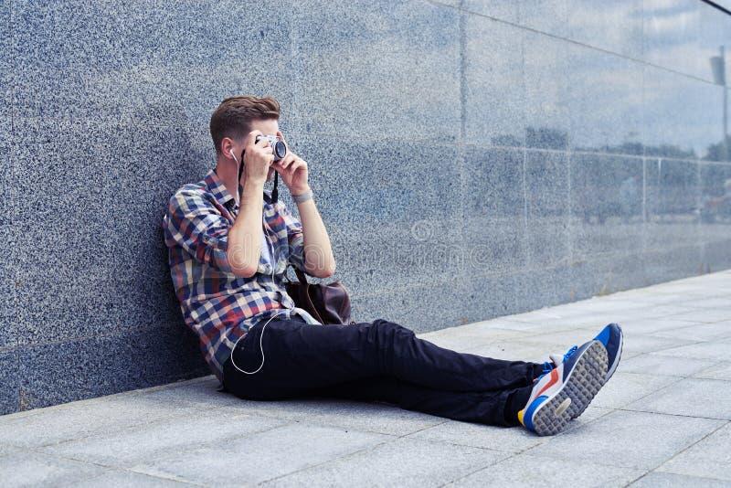 Jeune photographe beau se reposant dans le centre ville prenant des WI de photos photos libres de droits