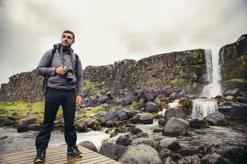 Jeune photographe de paysage à la cascade au parc national de Pingvellir photographie stock libre de droits
