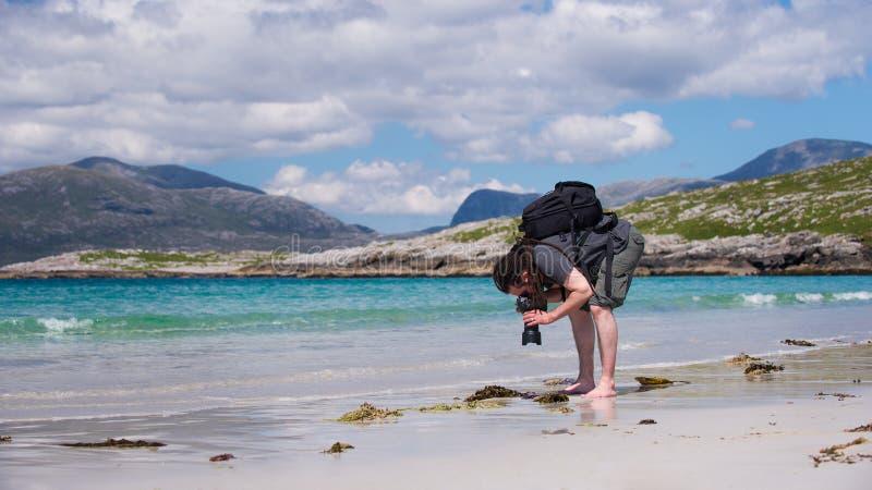 Jeune photographe masculin avec des dreadlocks à une plage blanche ensoleillée de sable, photo libre de droits