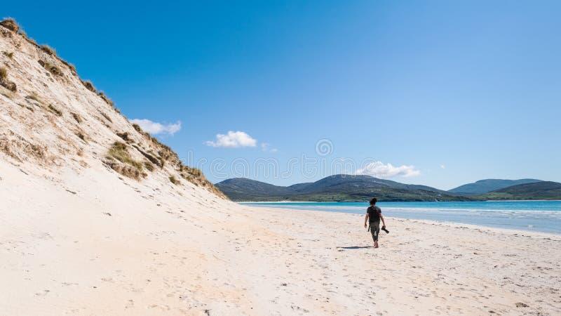 Jeune photographe masculin avec des dreadlocks à une plage blanche ensoleillée de sable avec de hautes dunes de sable, Luskentyre photos stock