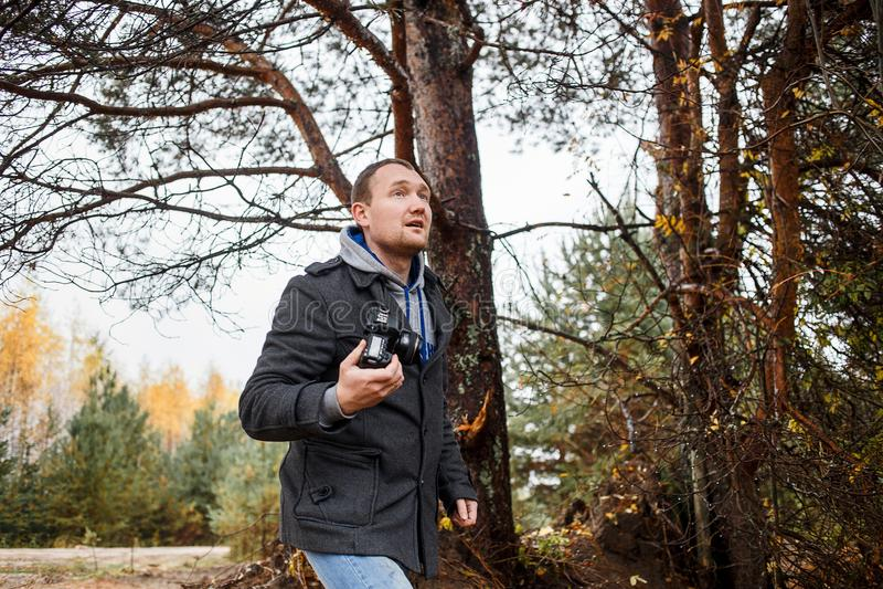 Jeune photographe photographiant dans la forêt d'automne photo libre de droits
