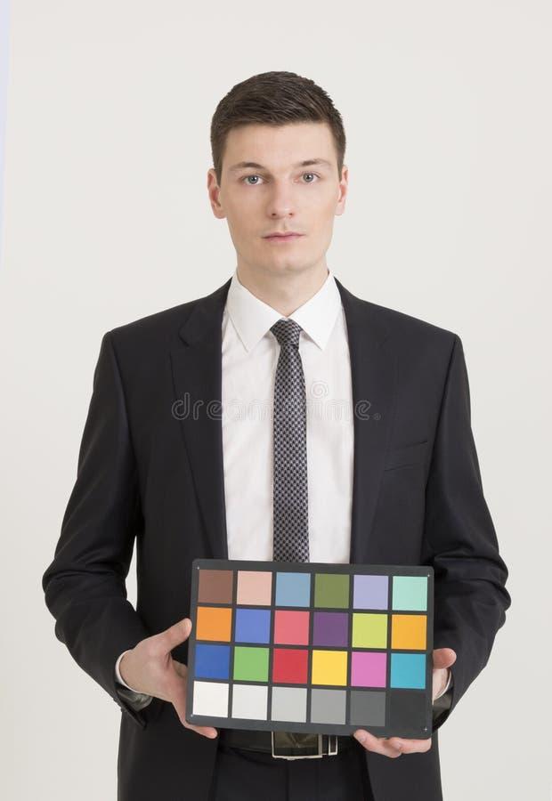 Jeune photographe tenant la carte de contrôleur de couleur photos stock