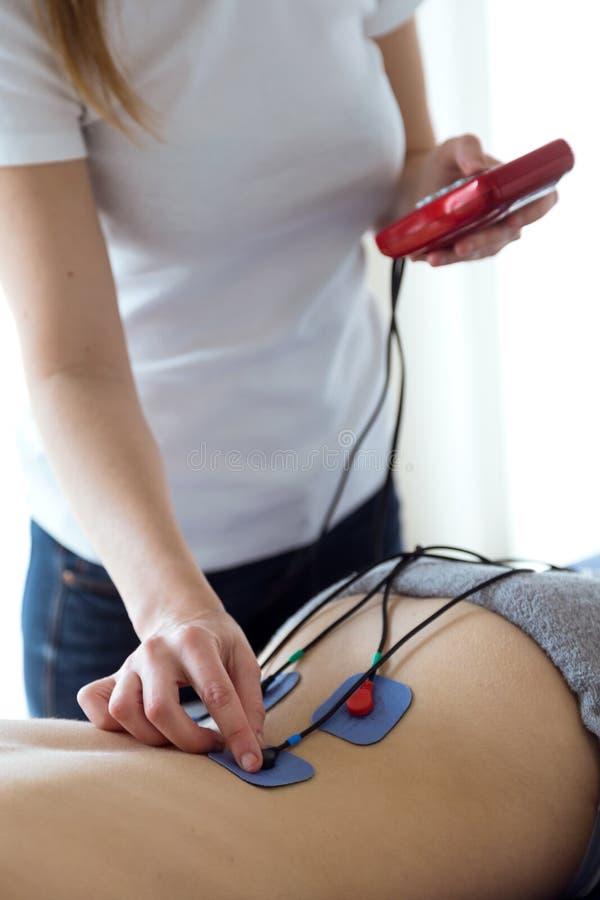 Jeune physioterapist s'appliquant l'électro stimulation dans la physiothérapie à un patient dans la physio- chambre image libre de droits