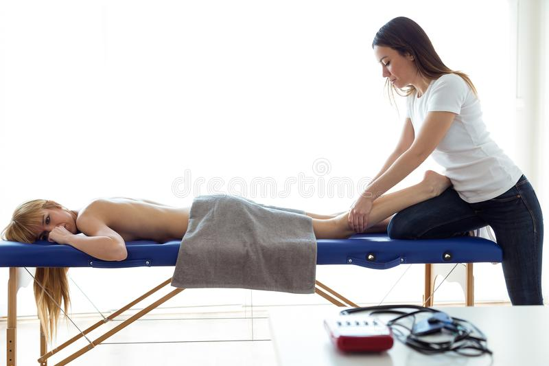 Jeune physiothérapeute faisant un traitement de jambes au patient dans une salle de physiothérapie photos stock