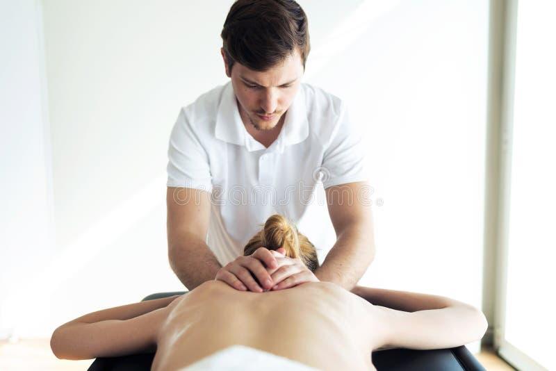 Jeune physioth?rapeute faisant un traitement arri?re au patient dans une salle de physioth?rapie images stock