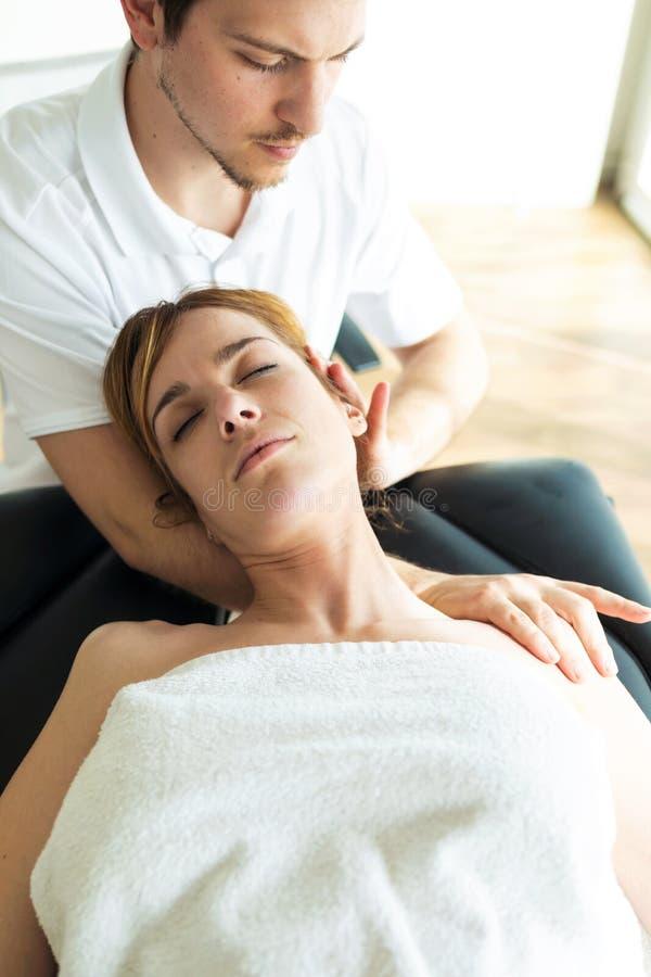 Jeune physioth?rapeute faisant un traitement de cou au patient dans une salle de physioth?rapie photographie stock libre de droits