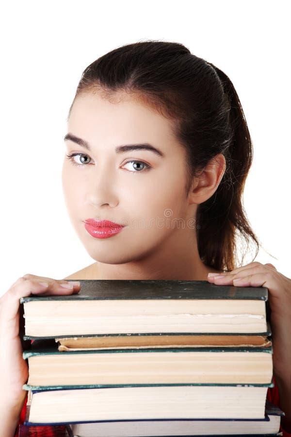 Jeune pile d'eith de femme d'étudiant de livres photographie stock