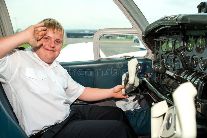 Jeune pilote handicapé saluant dans la cabine. image libre de droits